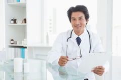 Happy doctor sitting at his desk Stock Image