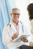 Happy Doctor Sitting With Patient In Clinic Royalty Free Stock Photo