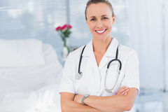 Happy doctor smiling at camera behind bed Royalty Free Stock Photography