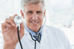 Happy doctor smiling at camera and showing his stethoscope Stock Image