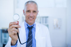 Happy doctor smiling at camera and showing his stethoscope Royalty Free Stock Photography