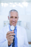 Happy doctor smiling at camera and showing his stethoscope Royalty Free Stock Image