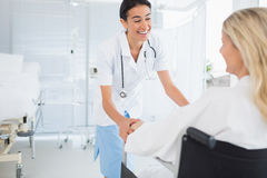 Happy doctor smiling at her patient in wheelchair Stock Photos