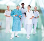 Happy doctor in surgical gown with his coworkers Stock Image