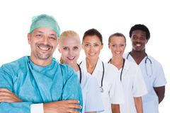 Happy doctor in surgical gown with his coworkers Royalty Free Stock Image