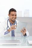 Happy doctor with tablet. Happy male doctor using tablet computer, sitting at desk Stock Images
