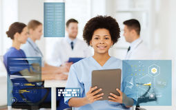 Happy doctor with tablet pc over team at clinic royalty free stock image