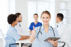 Happy doctor with tablet pc over team at clinic Royalty Free Stock Images