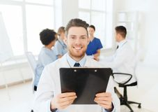 Happy doctor with tablet pc over team at clinic Stock Photo