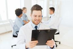 Happy doctor with tablet pc over team at clinic Stock Image