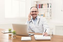 Happy doctor talking on phone with his patient. Happy doctor talking on phone with one of his patients and taking notes while working at his office. Always ready Royalty Free Stock Photography
