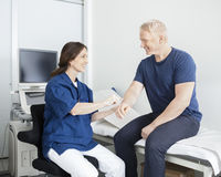 Happy Doctor Touching Male Patient's Hand In Clinic Stock Image