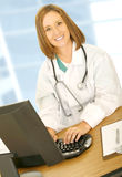 Happy Doctor Typing And Look At Camera Royalty Free Stock Photography