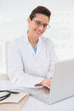 Happy doctor using laptop Royalty Free Stock Images