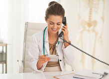 Happy doctor woman with calculator talking phone Royalty Free Stock Images