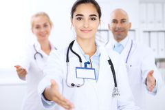 Happy doctor woman with medical staff at the hospital. Helping hand. Royalty Free Stock Photos