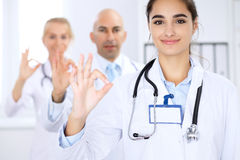 Happy doctor woman with medical staff at the hospital. Thumbs up and Ok sign Stock Photography