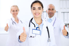 Happy doctor woman with medical staff at the hospital. Thumbs up and Ok sign Royalty Free Stock Image