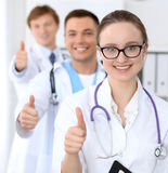 Happy doctor woman  with medical staff at the hospital. Thumbs up Stock Image