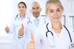 Happy doctor woman with medical staff at the hospital. Thumbs up. Stock Image