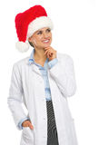 Happy doctor woman in santa hat looking on copy space Stock Images