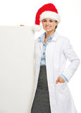 Happy doctor woman in santa hat showing blank billboard Royalty Free Stock Photography