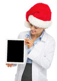 Happy doctor woman in santa hat showing tablet pc blank screen Royalty Free Stock Photos