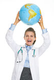 Happy doctor woman showing earth globe. Isolated on white Royalty Free Stock Photography