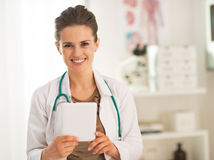Happy doctor woman using tablet pc in office Stock Photo
