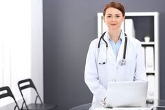 Happy doctor woman at work. Portrait of female physician using laptop computer while standing near reception desk at. Clinic or emergency hospital. Medicine royalty free stock photos