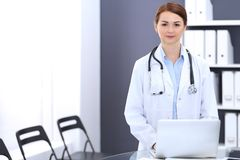 Happy doctor woman at work. Portrait of female physician using laptop computer while standing near reception desk at. Clinic or emergency hospital. Medicine stock photography