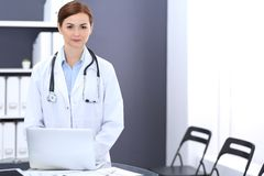 Happy doctor woman at work. Portrait of female physician using laptop computer while standing near reception desk at. Clinic or emergency hospital. Medicine stock photos