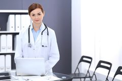 Happy doctor woman at work. Portrait of female physician using laptop computer while standing near reception desk at. Clinic or emergency hospital. Medicine stock photo