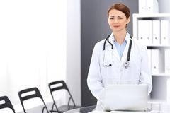 Happy doctor woman at work. Portrait of female physician using laptop computer while standing near reception desk at. Clinic or emergency hospital. Medicine royalty free stock images