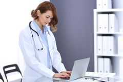 Happy doctor woman at work. Portrait of female physician using laptop computer while standing near reception desk at. Clinic or emergency hospital. Medicine royalty free stock image