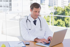 Happy doctor working on a laptop Stock Image