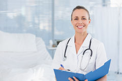 Happy doctor writing on clipboard behind bed Royalty Free Stock Images