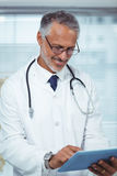 Happy doctor writing on clipboard. Happy doctor writing on a clipboard at home Stock Images