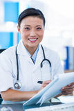 Happy doctor writing on a clipboard and smiling at camera Royalty Free Stock Image