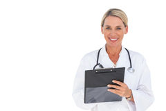 Happy doctor writing on a clipboard Stock Images