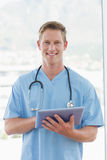 Happy doctor writing on clipboard beside windows Royalty Free Stock Photography