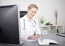 Happy Doctor Writing Medical Findings on her Table Stock Photography
