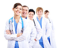 Happy doctors in hospital gowns in row Royalty Free Stock Image