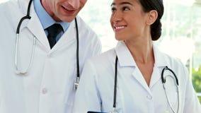 Happy doctors looking at clipboard stock video