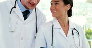 Happy doctors looking at clipboard stock footage