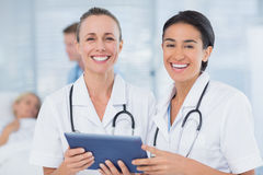 Happy doctors looking at clipboard while theirs colleagues speaks with patient Stock Photos