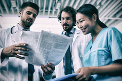 Happy doctors and nurse having discussion over medical reports Royalty Free Stock Image