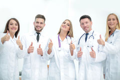 Happy doctors smiling and showing thumbs up. Stock Photos