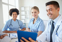 Happy doctors with tablet pc meeting at hospital. Medical education, health care, people, technology and medicine concept - group of happy doctors with tablet pc Royalty Free Stock Photo