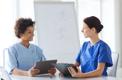 Happy doctors with tablet pc meeting at hospital Royalty Free Stock Photography